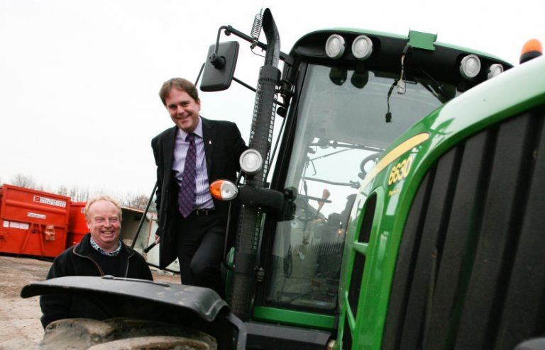 Two men stood with a green tractor